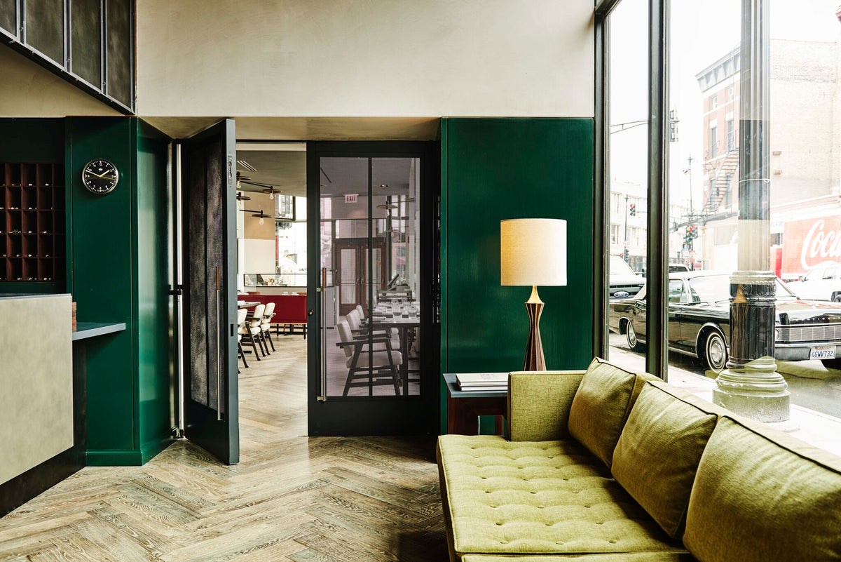 The Robey, Chicago - bright lobby with green walls, green couch, and large windows overlooking city street