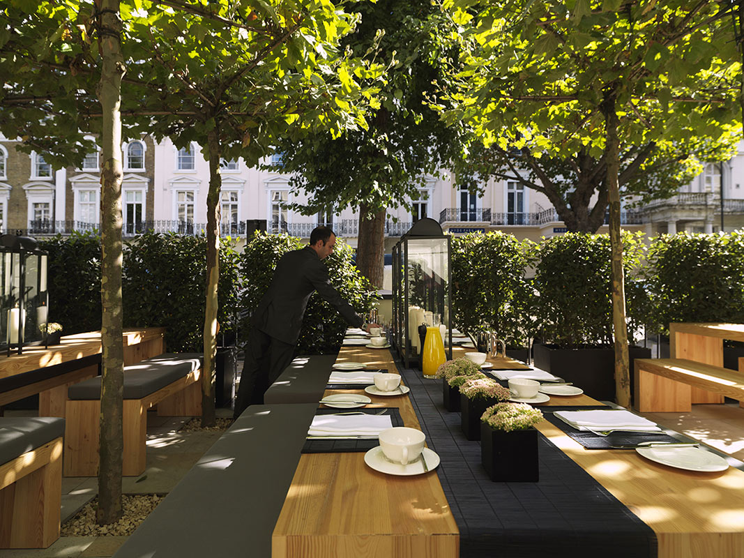 La Suite West, London, UK - hotel patio with outdoor dining under prim and proper trees