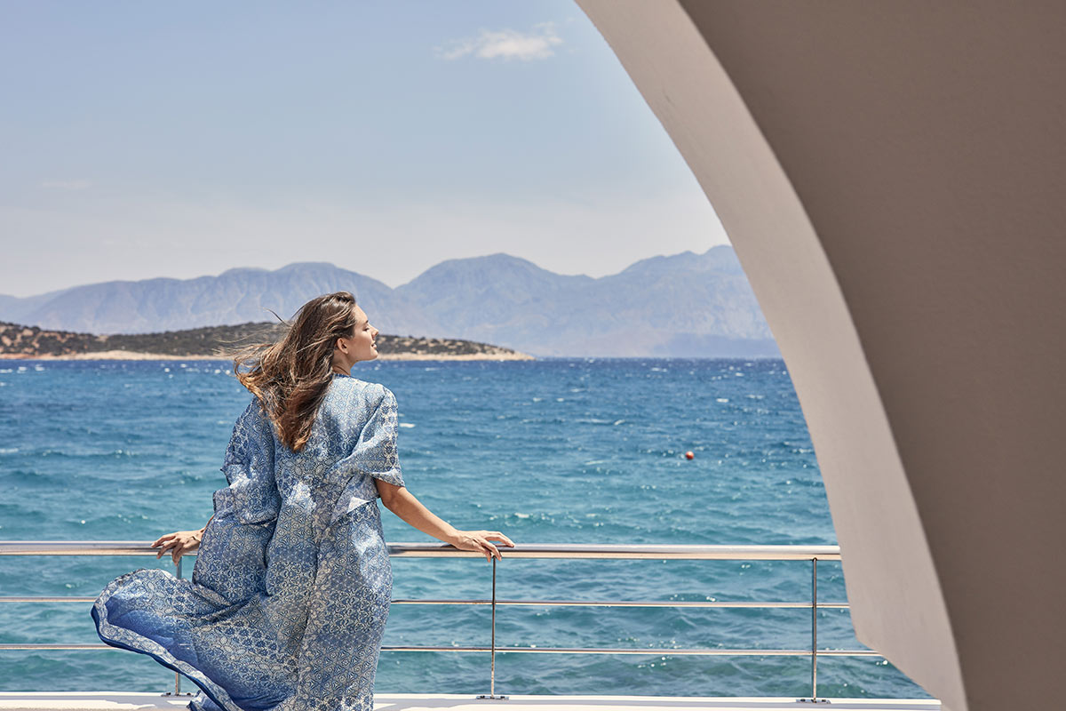 Minos Beach Art Hotel, Crete - woman standing on balcony overlooking turquoise water