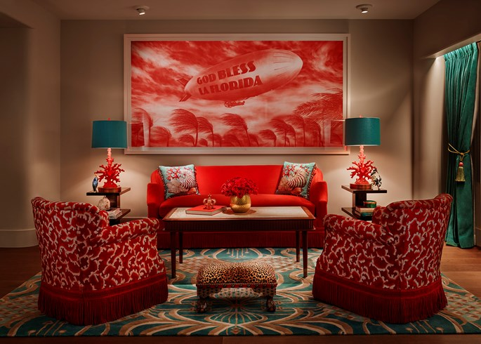 Faena Hotel, Miami Beach - hotel living room with red armchairs, red couch, and teal decorations