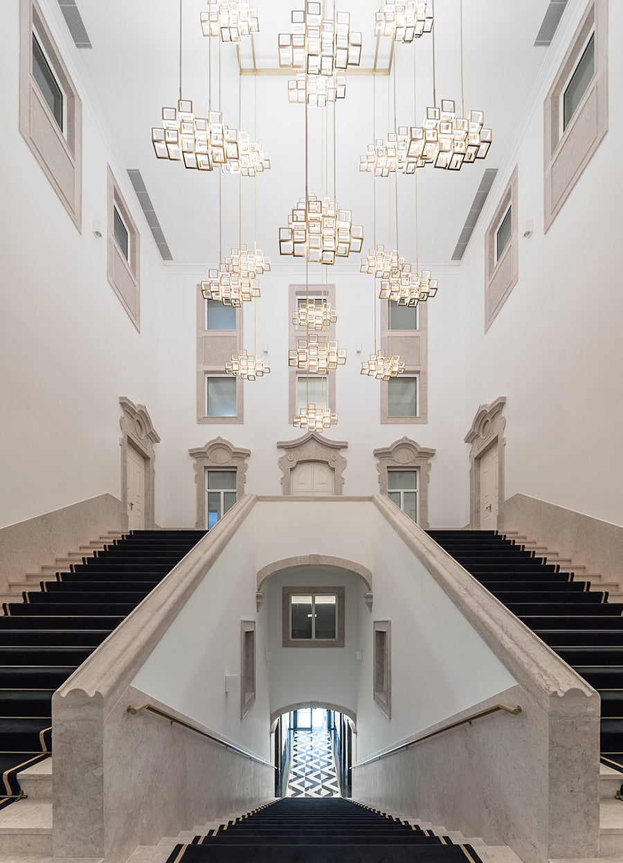 The Lumiares, Lisbon - hotel lobby with grand staircases, windows, and intricate modern chandeliers