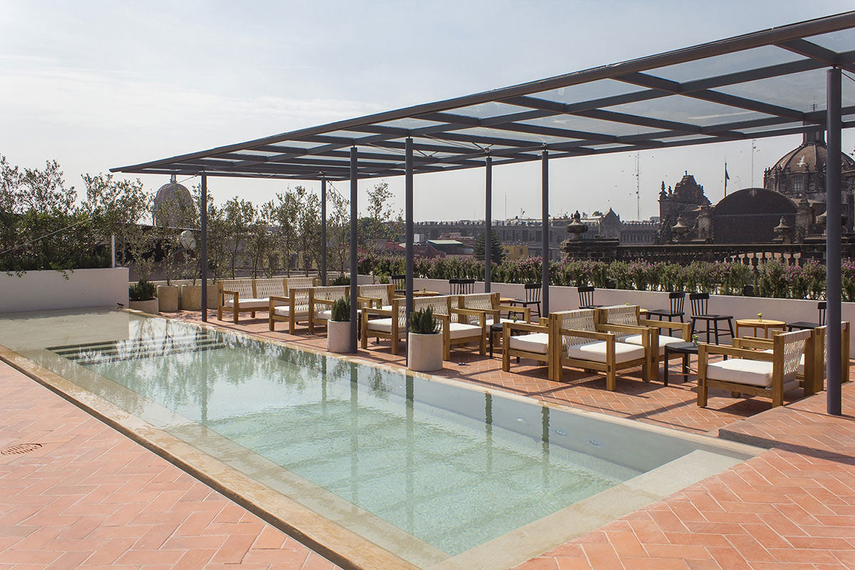Círculo Mexicano, Mexico City - hotel rooftop pool with minimalist wooden outdoor chairs overlooking historic city