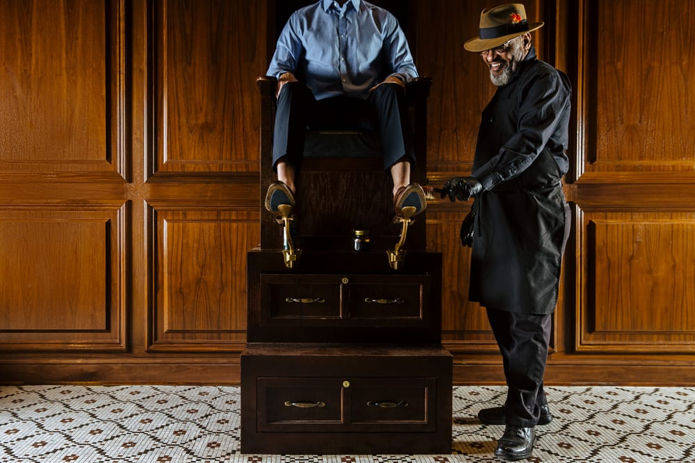 The Adolphus Hotel, Dallas - man sitting in an antique shoeshine chair with another man shining his shoes