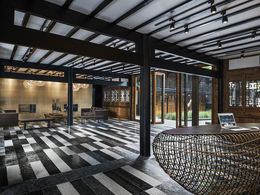 The Temple House, Chengdu - hotel lobby with dark tile floors, dark wood beams, and windows overlooking temple courtyard