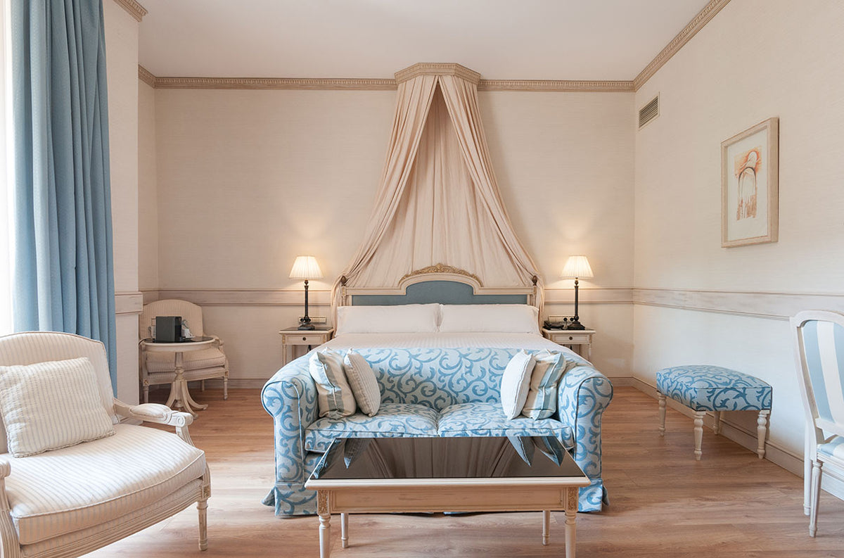 Hotel Eugenia de Montijo, Toledo - hotel room with off-white and powder blue accents and a circular canopy bed