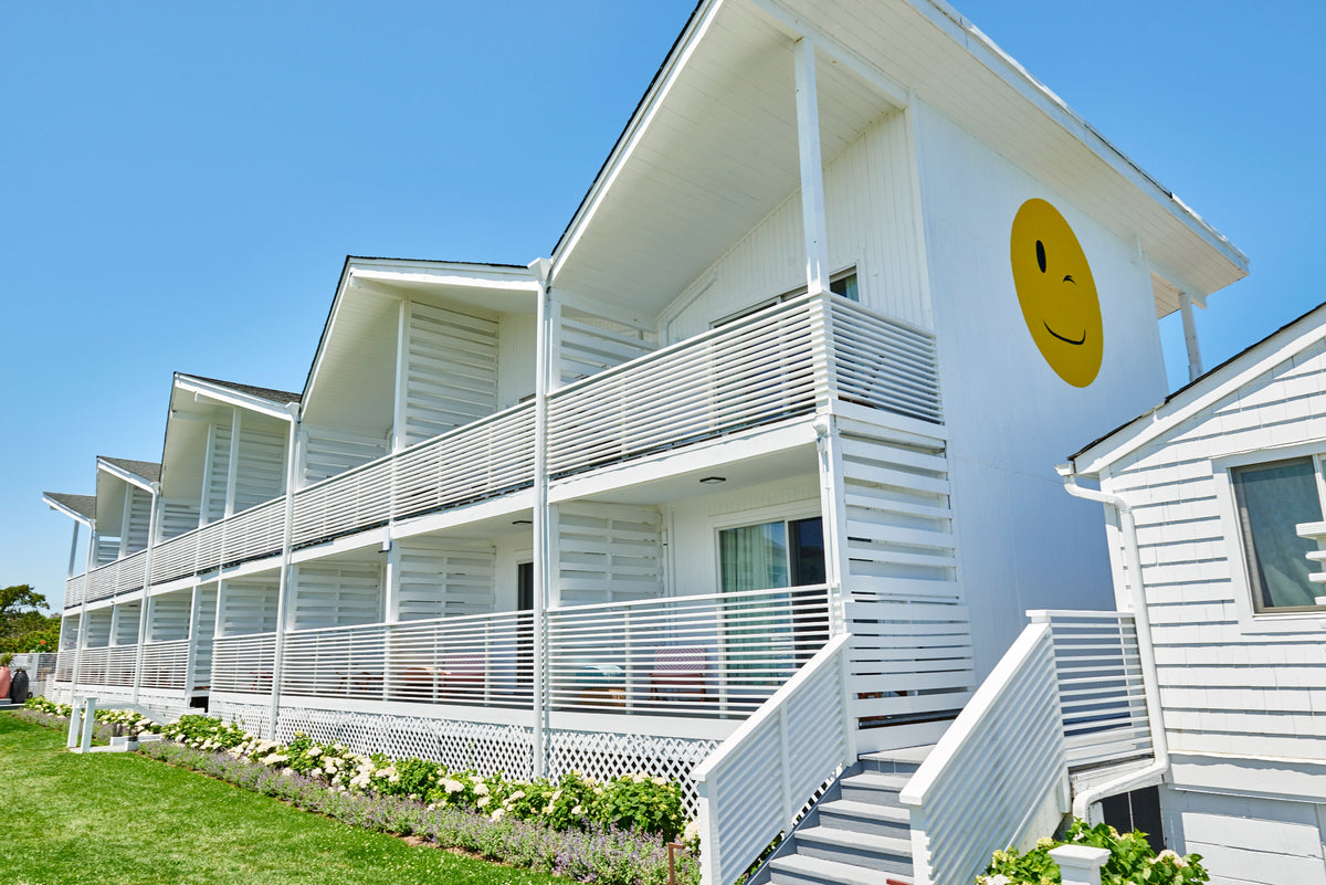 Hero Beach Club, Montauk - white motel style building with privet balconies and a yellow smiley face on side wall