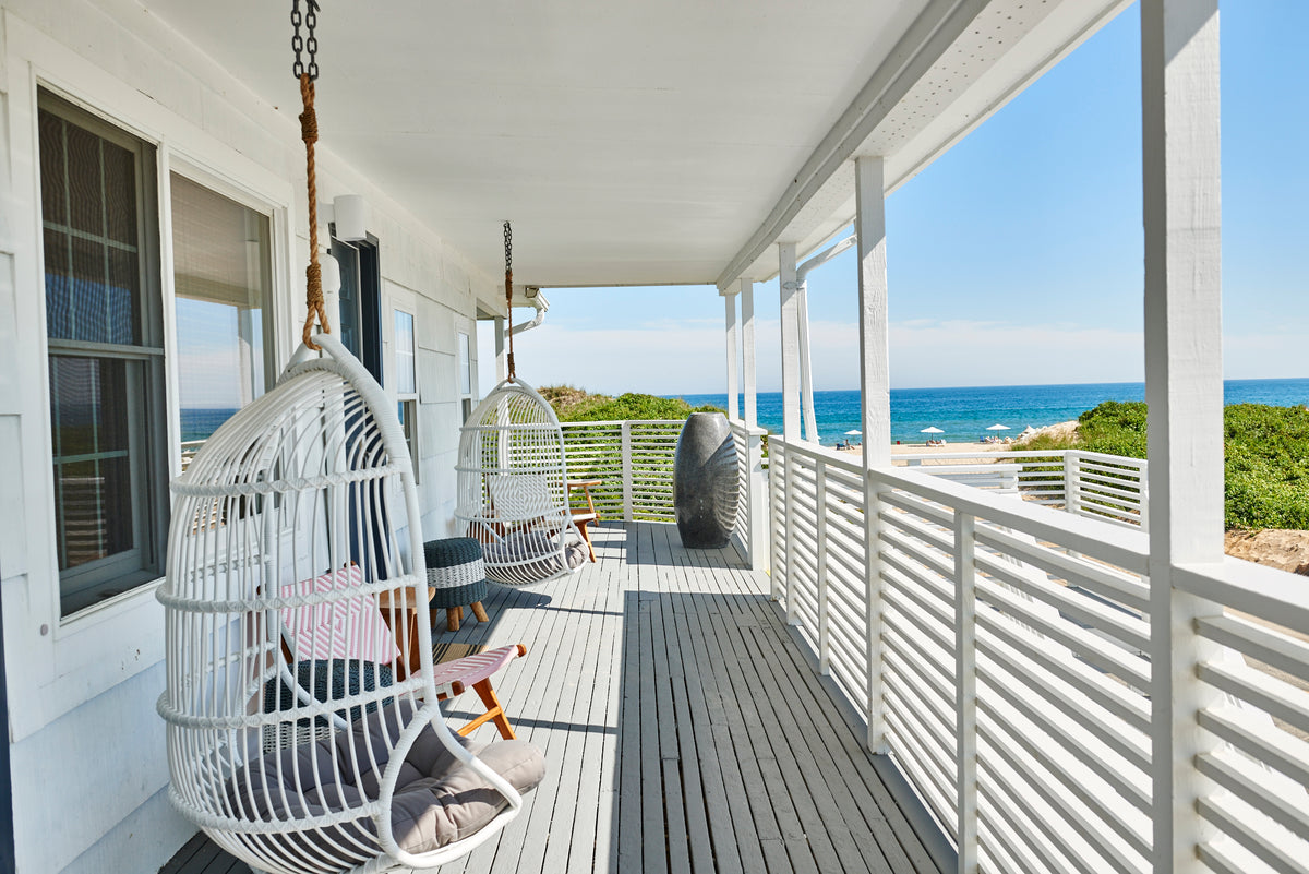 Hero Beach Club, Montauk - white balcony with white hanging wicker chairs, and view overlooking Atlantic Ocean