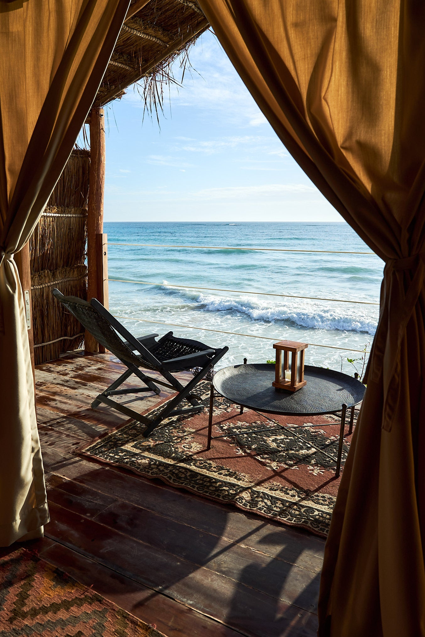 Habitas, Tulum - rustic bungalow patio over blue ocean with intricate rugs and deck chairs