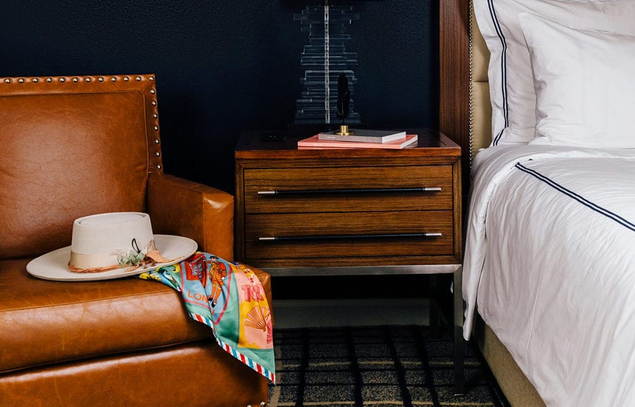 The Adolphus Hotel, Dallas - close up of hotel room bedside table with books and brown leather chair with hat and scarf