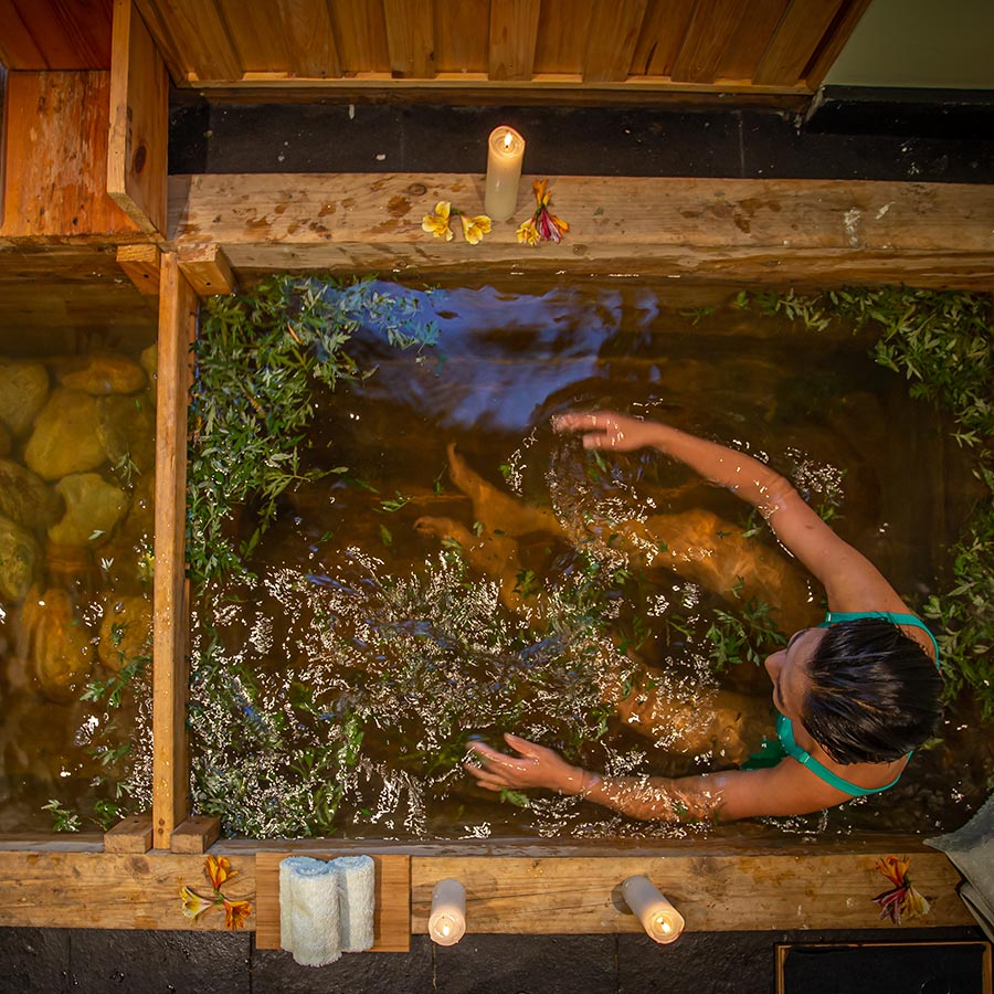 Bhutan Spirit Sanctuary, Bhutan - woman in a herbal spa tub with plants floating in the water and candles around the tub