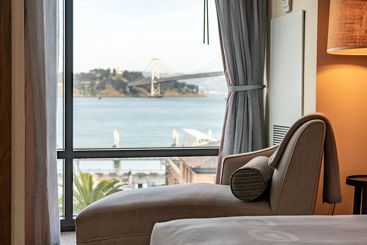 Hotel Vitale, San Francisco - hotel room with close up on armchair and window overlooking Golden Gate Bridge