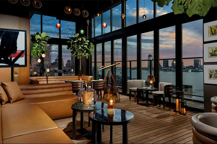 Hotel Hugo, NYC - hotel lounge with large leather couches, dark coffee tables, and large windows overlooking the Hudson River at sunset