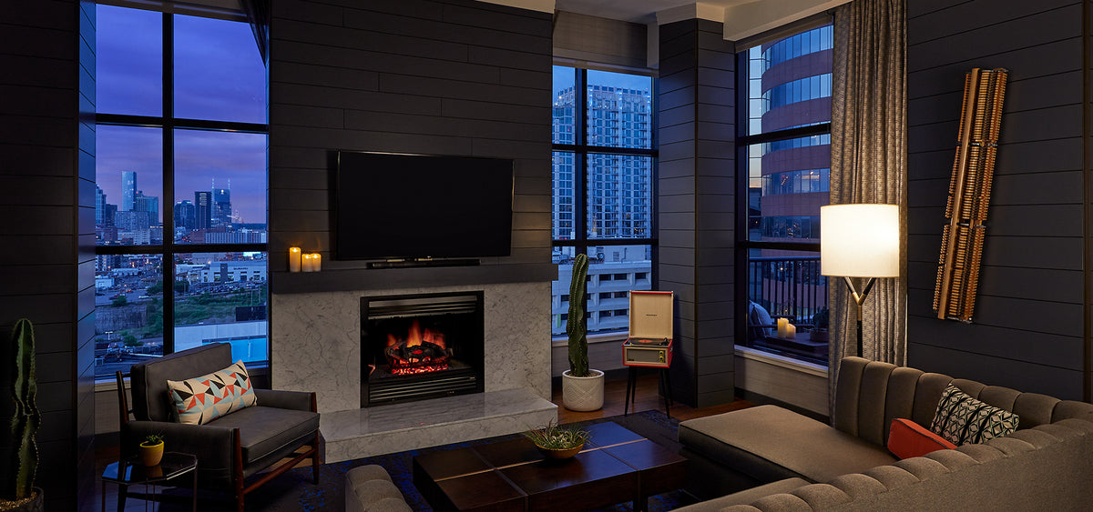 Hutton Hotel, Nashville - hotel room with couch, fireplace, armchair, and huge windows overlooking city at sunset