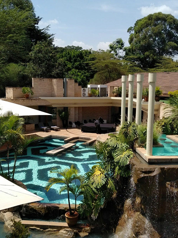 Tribe, Nairobi - hotel pool with naturalistic landscaping and palm trees