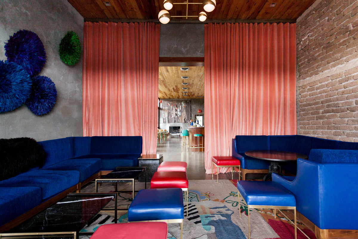 Thunderbird Hotel, Marfa - hotel lounge with dark blue and red theme with exposed brick walls