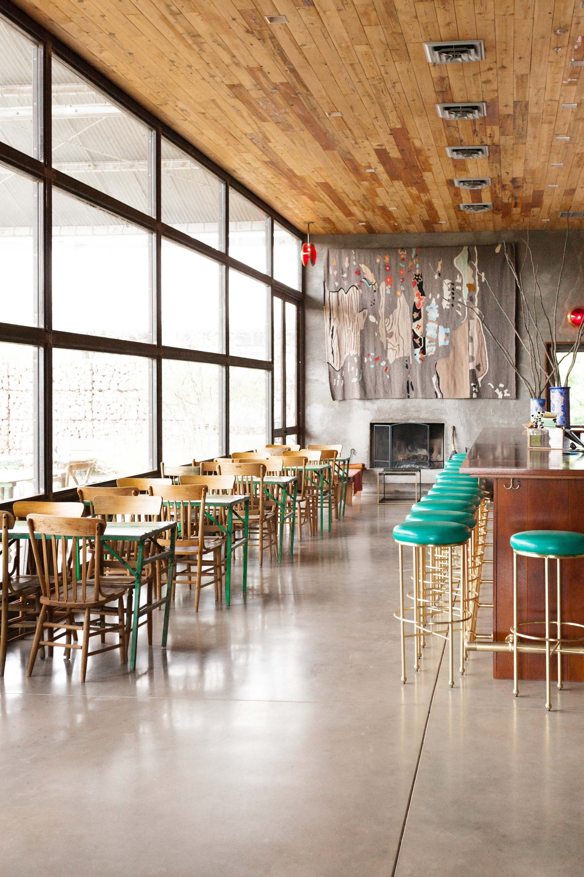 Thunderbird Hotel, Marfa - hotel restaurant with wood plank ceilings, rustic chairs and tables, and bar.