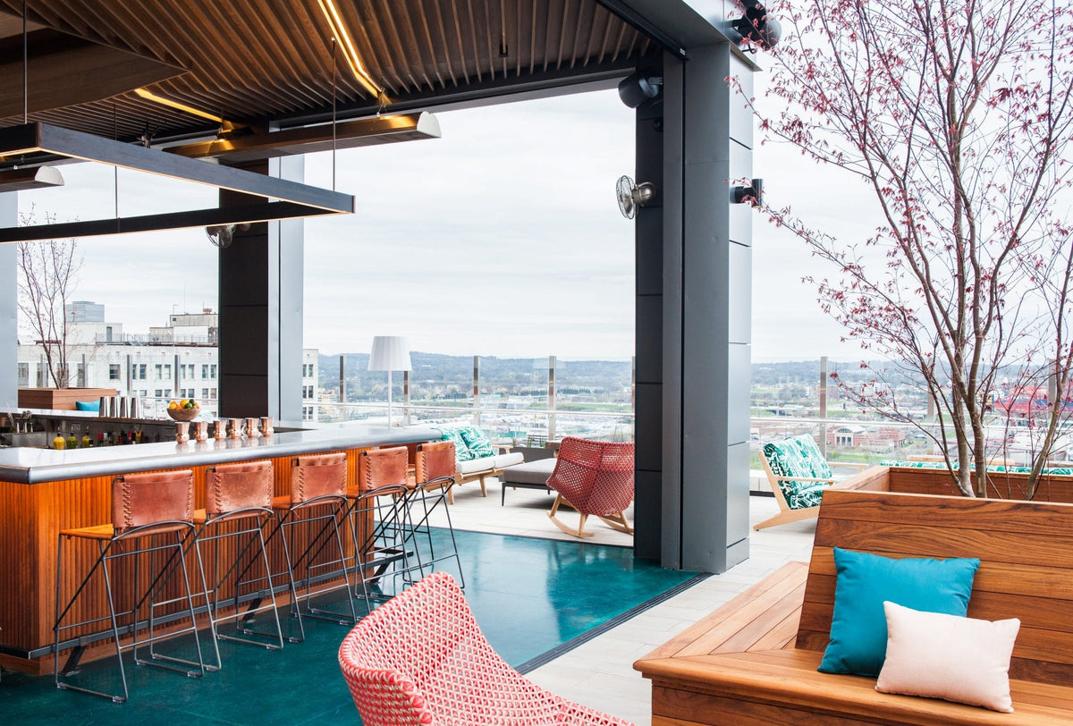 Noelle, Nashville - Rare Bird rooftop bar with barstools, wooden benches, and city view