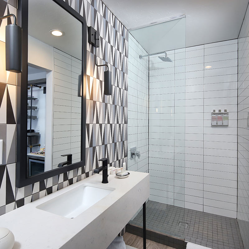 The Tuxon Hotel, Tucson - hotel bathroom with geometric tile wall, walk-in shower, and sink