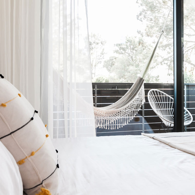 Twelve Senses Retreat, Encinitas - close up of hotel bed with decorative stitched pillow and balcony with hammock