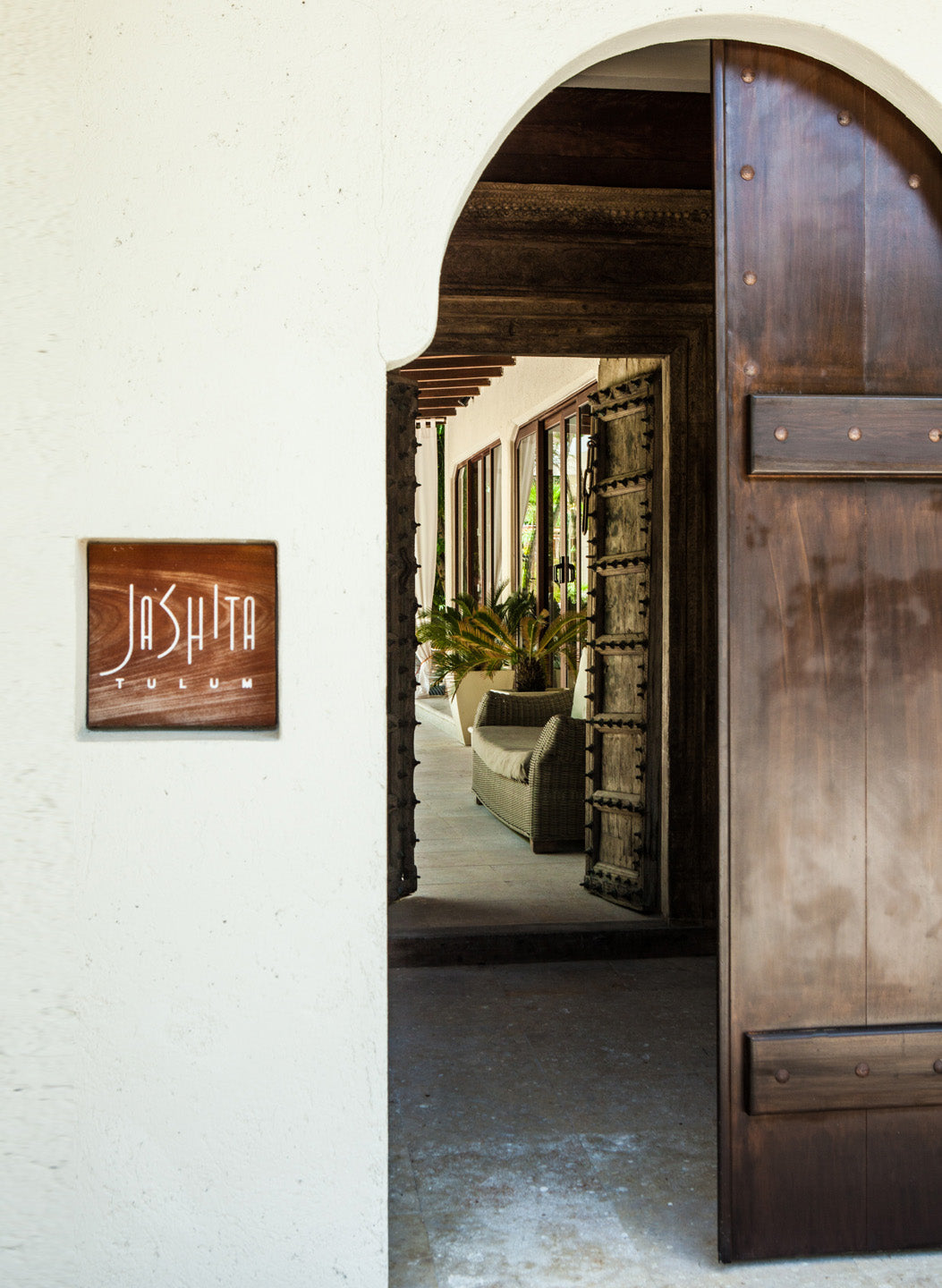 Jashita Hotel, Tulum - close up of hotel entrance with wooden Jashita sign and large dark wooden doors