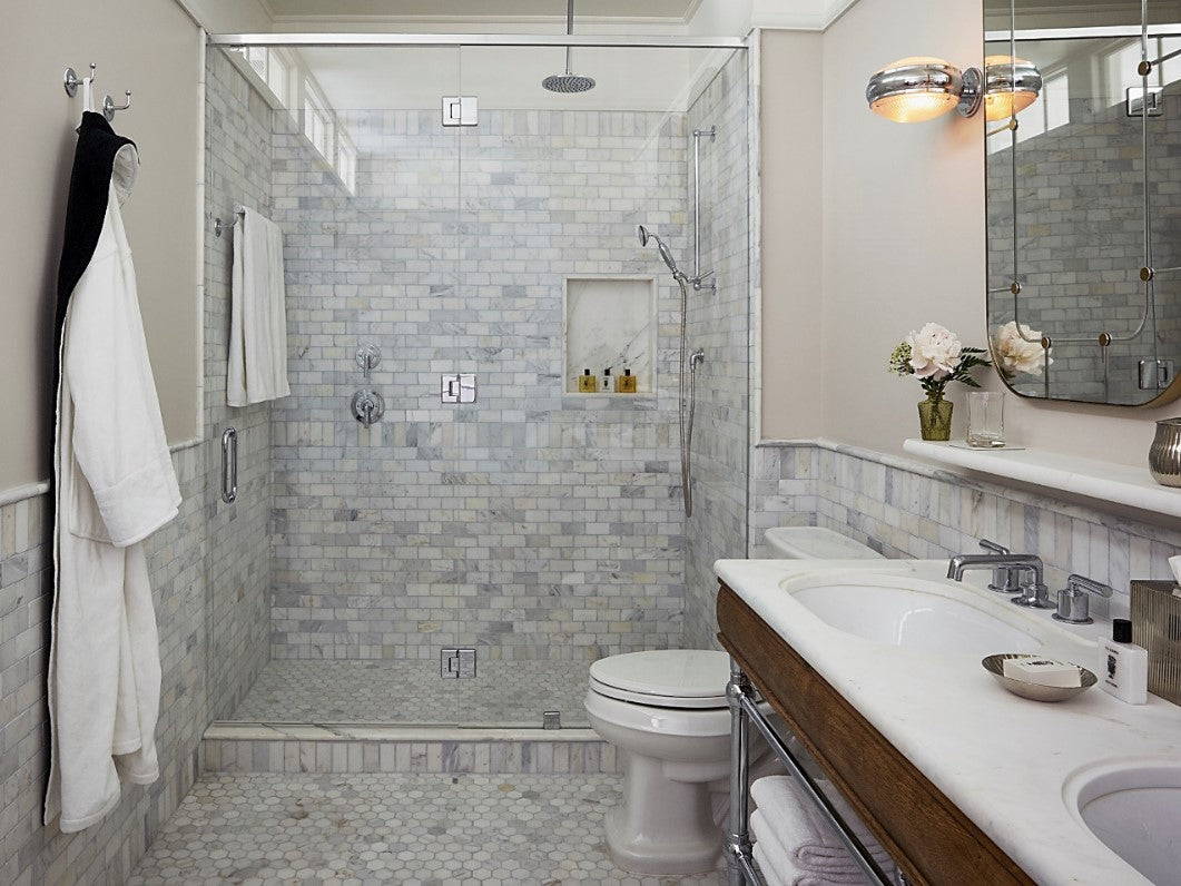 The Beekman, NYC - hotel bathroom with modern white tiling and walk-in shower