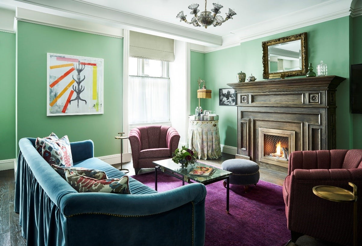 The Beekman, NYC - hotel living room with plush velvet seating, green walls, and an antique fireplace