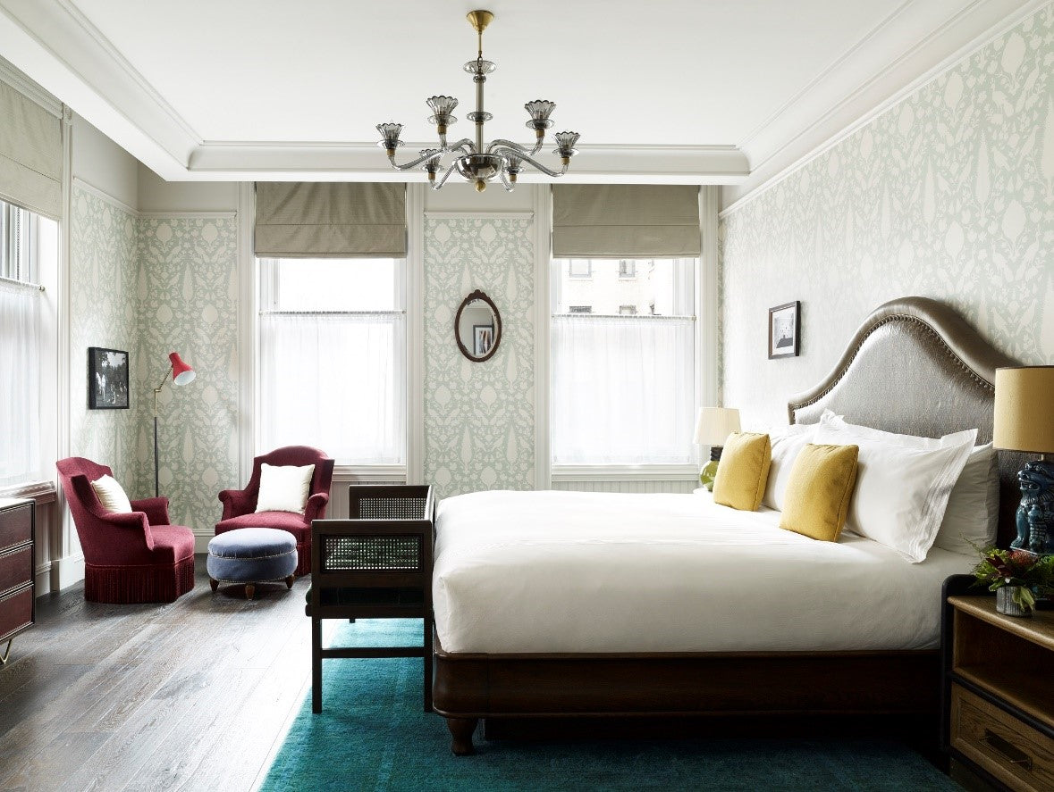 The Beekman, NYC - hotel room with patterned wallpaper, large bed, and 2 red velvet armchairs