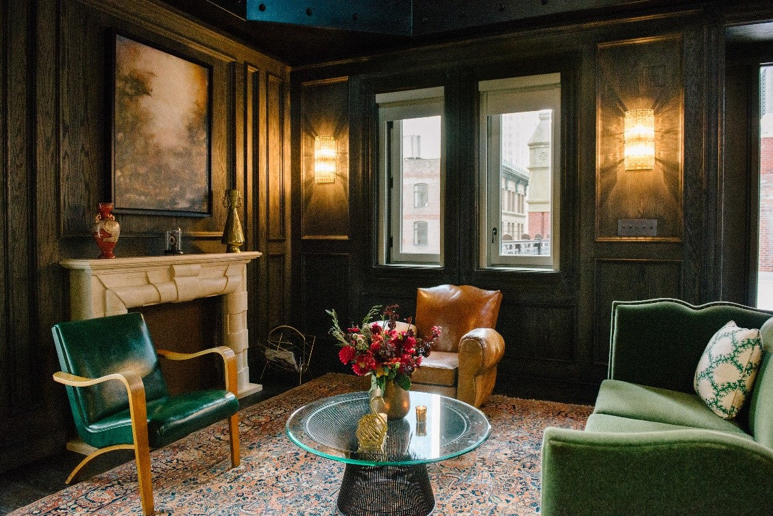 The Beekman, NYC - hotel lounge with dark green furniture, green walls, and antique fireplace