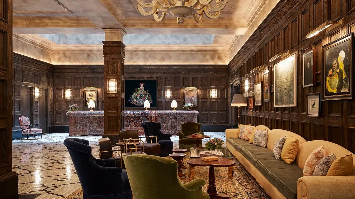 The Beekman, NYC - ornate hotel lobby with plush velvet armchairs and couches with dark wood walls and hanging portraits