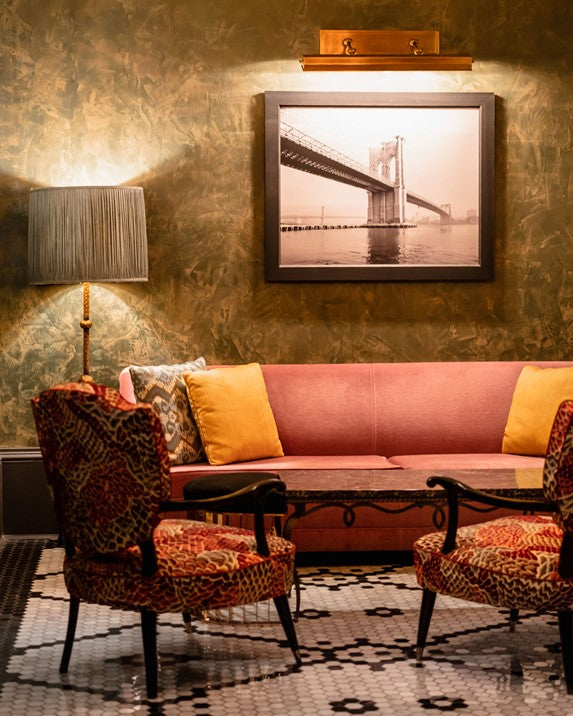 The Beekman, NYC - hotel lobby with ornate orange seating and dark wallpapered walls
