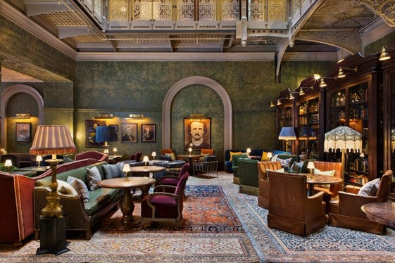 The Beekman, NYC - hotel lobby with ornate armchairs, dark wood bookcases, dark green walls, and an Edgar Allen Poe portrait