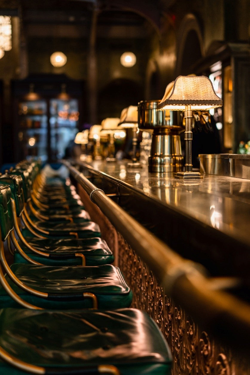 The Beekman, NYC - The Temple Court restaurant bar with dark green leather barstools along a vintage dark wood bar