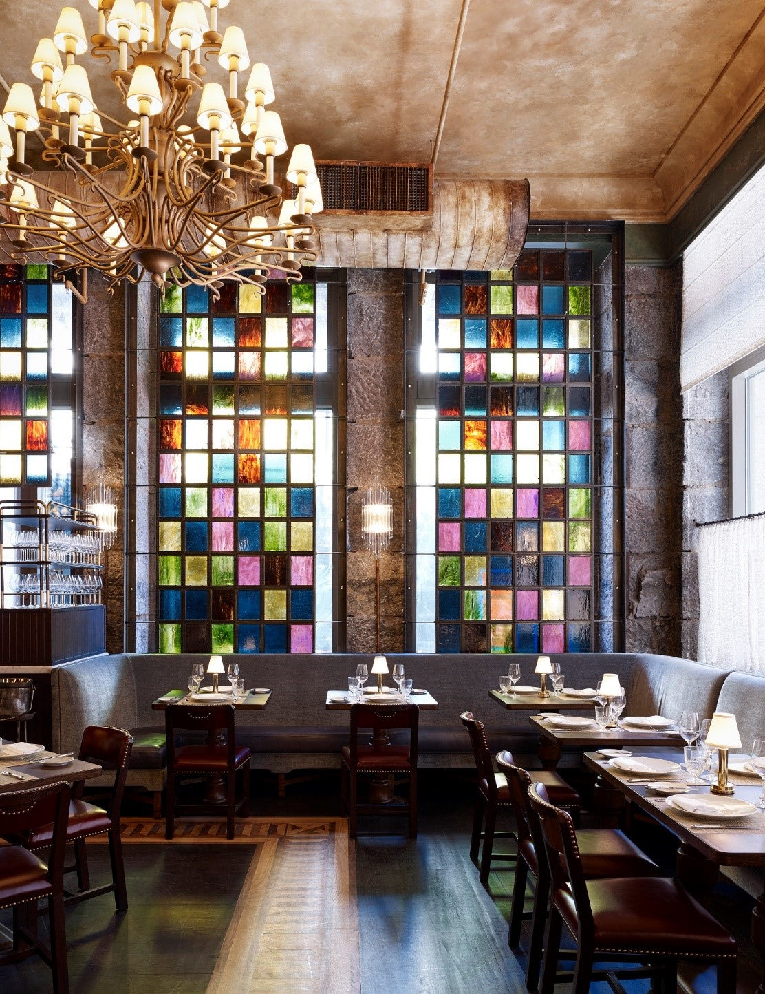 The Beekman, NYC - Temple Court restaurant with set tables, large stained-glass windows, and an elegant chandelier