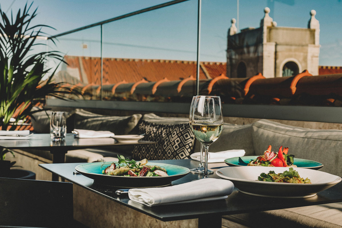 The Lumiares, Lisbon - hotel rooftop restaurant with tables set, 3 dishes on one table, and view of city roofs