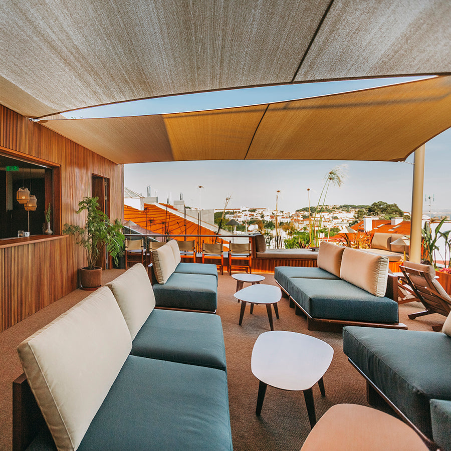 The Vintage Hotel & Spa, Lisbon - hotel rooftop lounge with couch seating, coffee tables, canvas awning, and city view