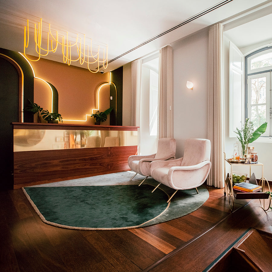 The Vintage Hotel & Spa, Lisbon - hotel room with suede armchairs, hanging neon lights, and bar cart