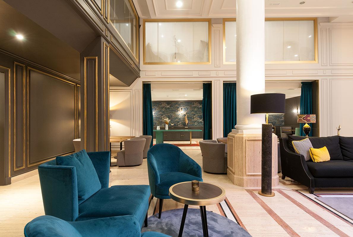 Hotel Eugenia de Montijo, Toledo - hotel lounge with velvet chairs and couches, turquoise accents, and large balcony windows