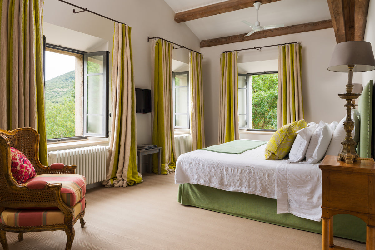 La Fraissinède, Val de Dagne, France - villa room with large bed, wooden beam ceilings, and large windows overlooking green mountainous countryside