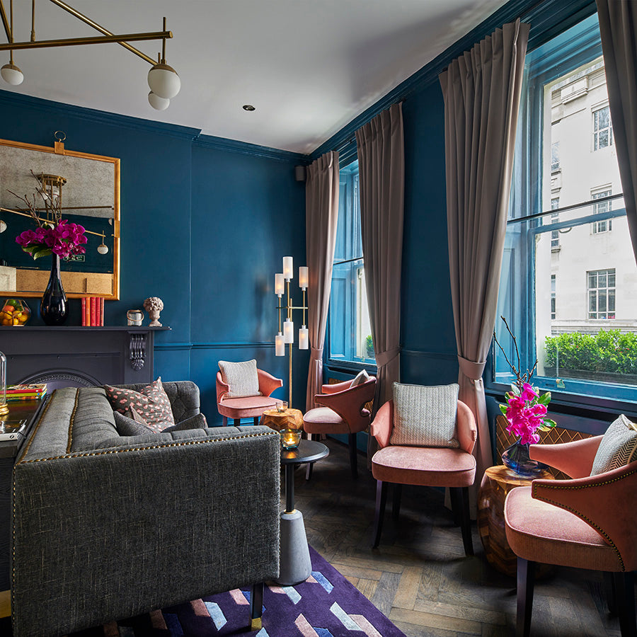The Academy Hotel, London - hotel room with blue walls, grey couch, pink armchairs, and windows overlooking London buildings