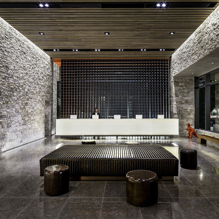 EAST, Miami - hotel lobby and reception desk with stone walls, black couch, and wooden plank ceiling