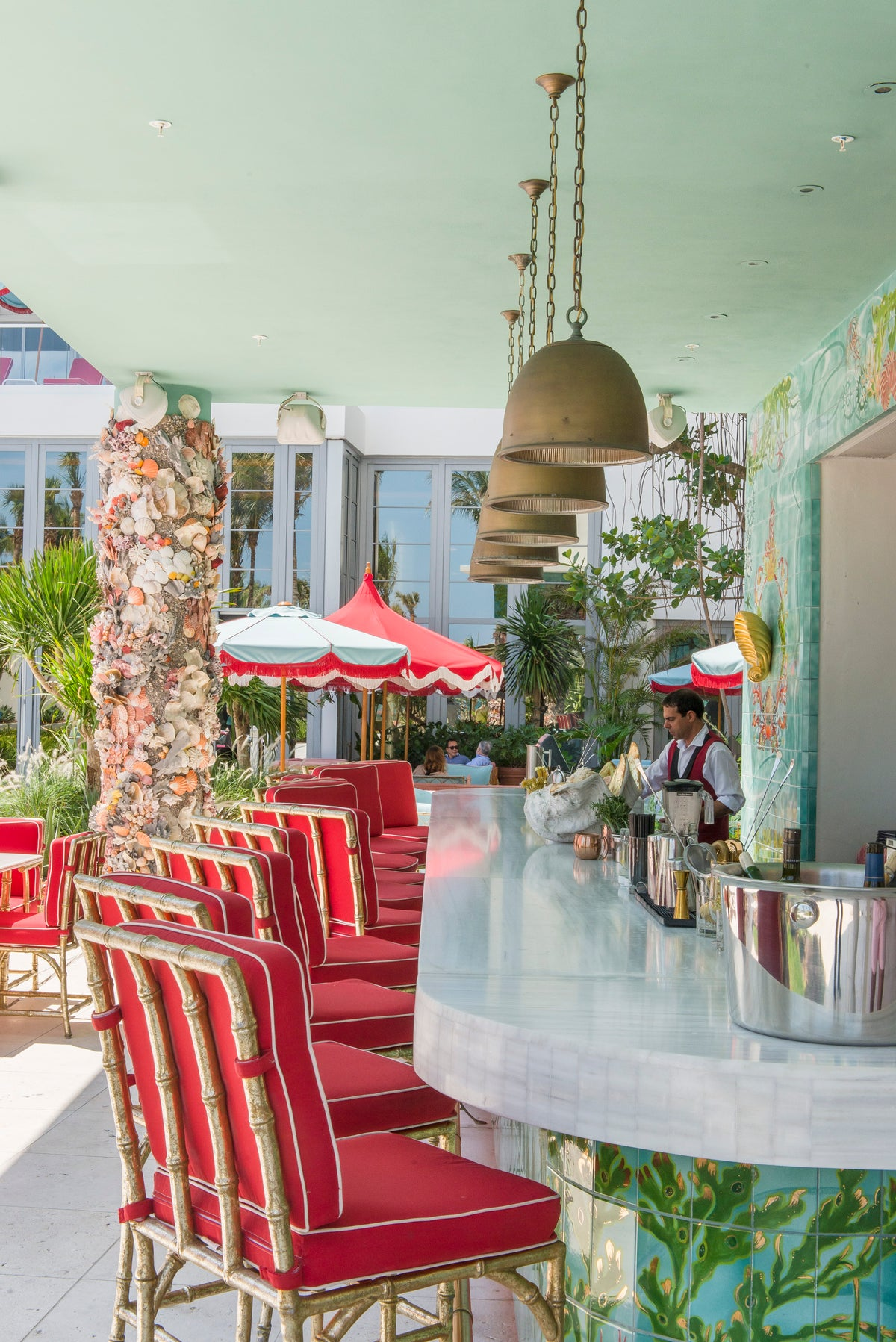 Faena Hotel, Miami Beach - white stone hotel bar with red tiki bar stools and a bartender making a drink