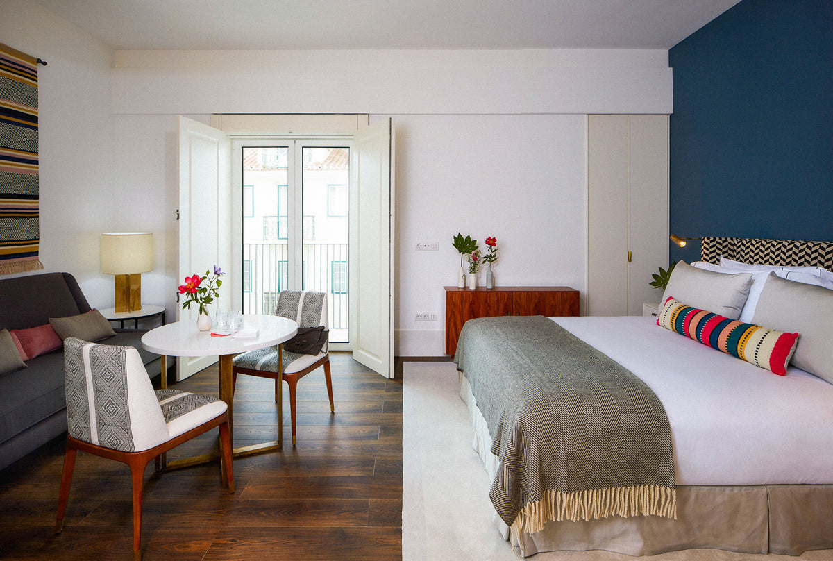 The Lumiares, Lisbon - contemporary hotel room with bed, table, chairs, couch, blue accent wall, and private balcony