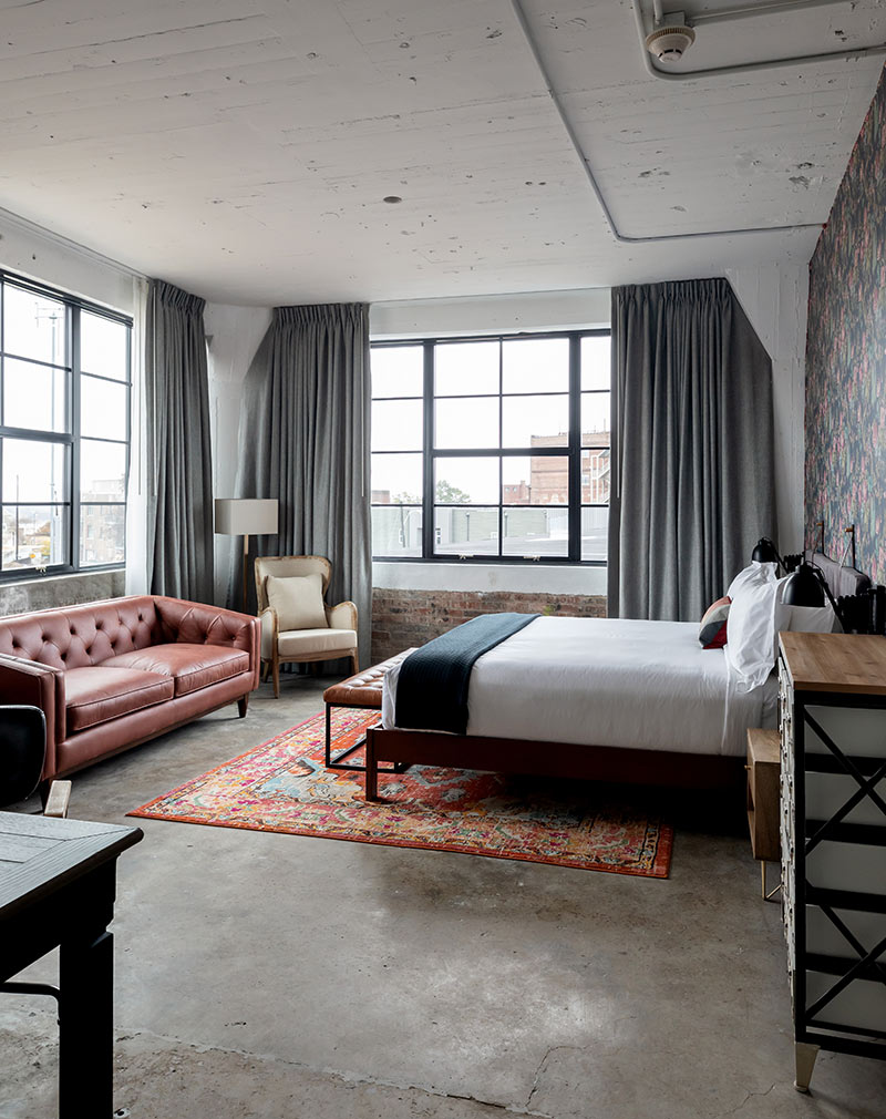 ARRIVE Memphis, Memphis, TN - hotel room with dark industrial decor, bed, red leather couch, and large windows