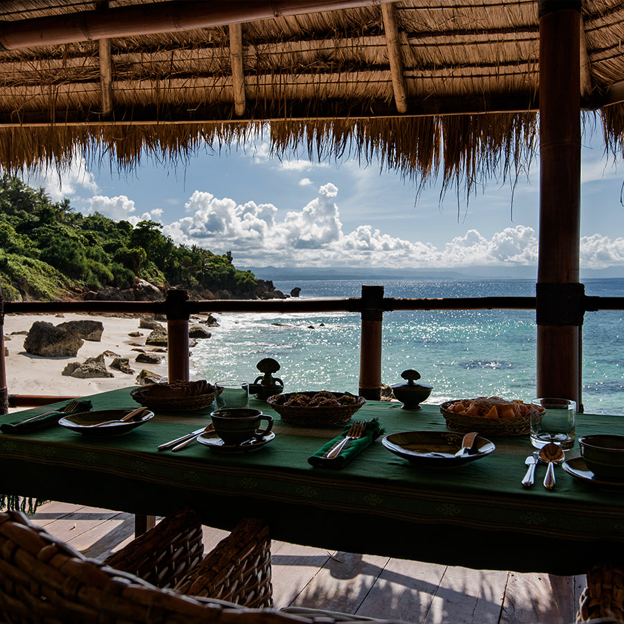 Nihi Sumba, Sumba Island- hotel restaurant patio with set tables, thatch roof, and view of Indian Ocean and jungle greenery