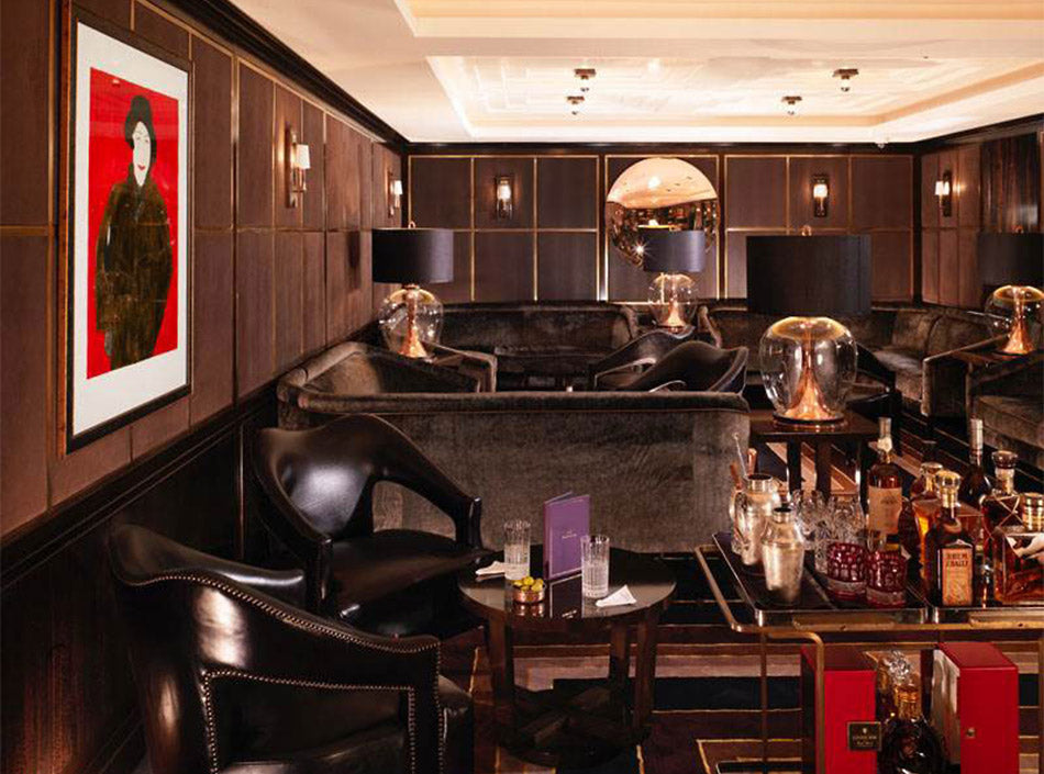Flemings Mayfair, London - vintage dark wood hotel bar with armchairs, couches, and alcohol bottles