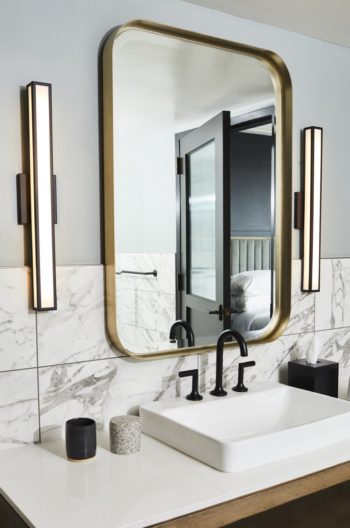 Noelle, Nashville - hotel bathroom with vintage mirror and light fixtures, classic white sink, and marble tiling