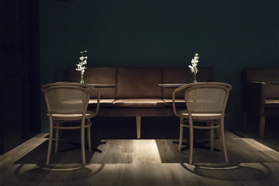 Yurbban Trafalgar, Barcelona - hotel restaurant seating with brown couch, wicker chairs, tables topped with a flower, and dark teal walls