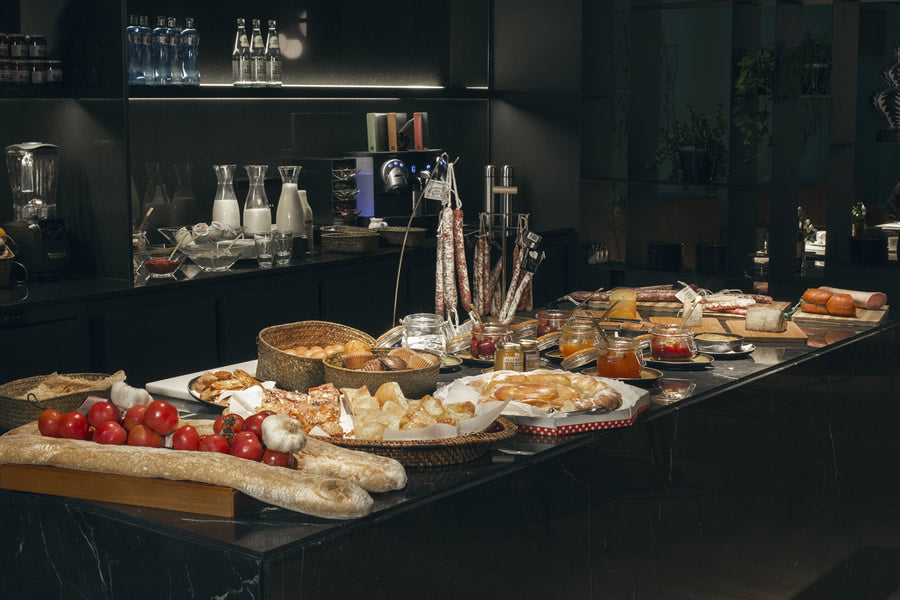 Yurbban Trafalgar, Barcelona - breakfast buffet spread with bread, sausages, tarts, jams, and cheeses