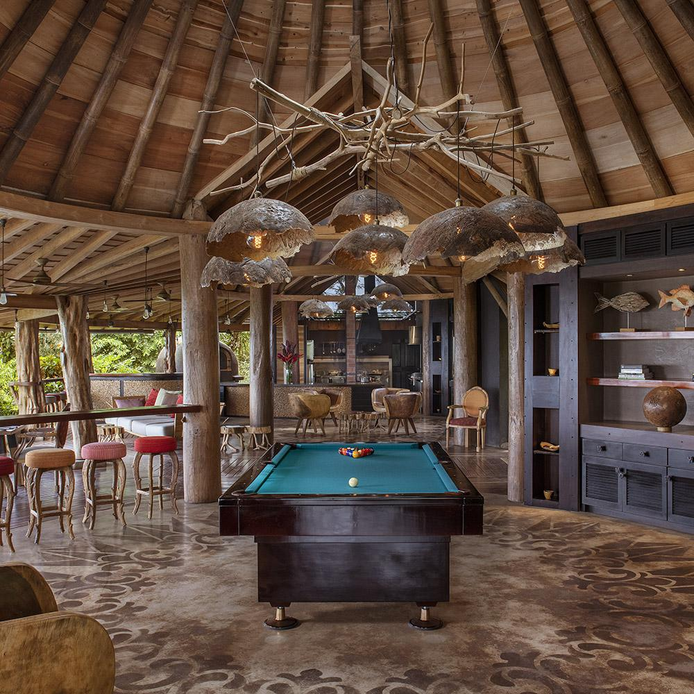 Origins Lodge, Bijagua - open air patio with chairs, bookcases, and a pool table under a natural sculpture light fixture