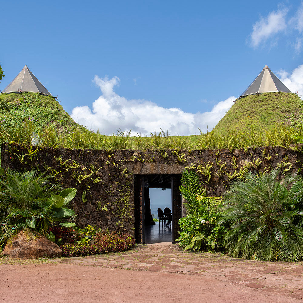 Origins Lodge, Bijagua - entry way with old stone wall covered in growing plants and topped with conical grassy mounds